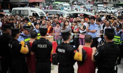 身着鲜红色囚服、拖着沉重的脚镣,7名盗抢嫌犯日前在特警的押解下,到贵阳闹市指认现场,引发群众围观。
