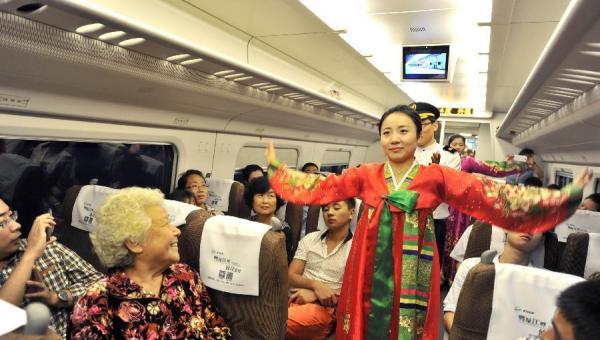 9月1日,在丹东开往沈阳的首发动车组上,几名身着朝鲜族服装的乘务人员为旅客表演节目。 新华社 图