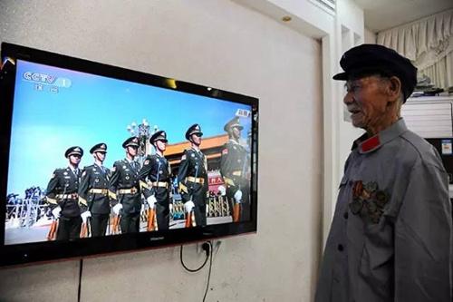 在江西省万载县鹅峰乡多江村,95岁抗战英雄徐桃生正在收看抗战胜利70周年阅兵盛况。徐桃生19岁参军,曾参加过著名的浙江金华保卫战。3日,他特意穿上红军的服装,把珍贵的勋章挂在胸前。看着阅兵场上的年轻人,老人笑得像个孩子。
