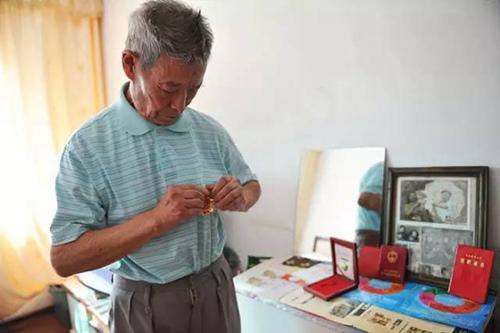 辽宁省抚顺市,90岁的老军医韩树清在阅兵式开始前整理衣装、佩戴勋章;他仿佛回到了1949年自己作为后勤部队参加检阅的那一刻。