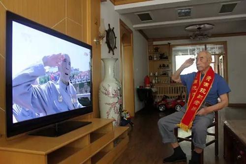 """94岁黄埔老兵焦正辉,毕业于黄埔军校七分校17期,曾当过高射炮兵,参加过武汉保卫战和重庆保卫战。由于当炮兵的缘故,焦正辉耳朵不好。9月3日守在电视机前的他,听不清背景音,只能静静地看,当看到电视里部队接受检阅敬礼时,他也保持足足半个小时的敬礼姿势,孩子们怕他身体受不了,劝他把手放下。歇了一会儿后,焦正辉还是对着电视敬礼。当看到电视里出现高射炮时,他激动地指着电视说:""""现在的武器真的比我们那时候好多了,再也不怕挨欺负了。"""""""