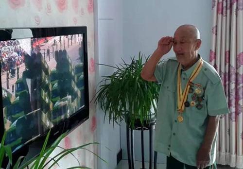 """96岁抗日老兵张宝宪曾跟随部队辗转半个中国,负伤32次。当看到电视里升国旗时,这位年过九旬的老人哭了起来,什么话也说不出来。当看到电视里的出现坦克时,张宝宪问儿子:""""这些坦克是咱们的吗?""""张宝宪说:""""我要活到下一个阅兵,躺着也要去看!"""""""