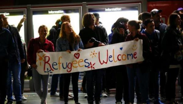 """在德国法兰克福火车站,友善的当地人手持""""欢迎难民""""(Refugees Welcome)的横幅,欢迎进入德国的叙利亚难民们,并向他们派发糖果。"""