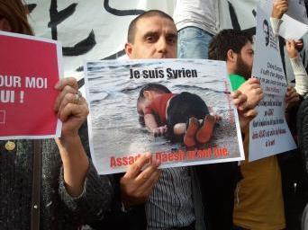 叙利亚难民Ammar Kharboutli在巴黎共和广场的游行示威中手举艾兰遇难时的照片。