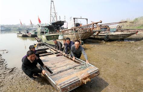 休渔季来临,渔民将渔船拖上岸