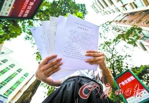 陈蜜斯拿着近段时刻打讼事的材料。广州日报记者苏豪杰 摄