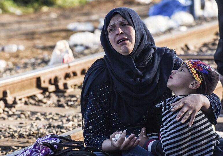 匈牙利封闭首要路线,一位来自中东的灾黎妇孺抱着孩儿痛哀。(法新社图像)