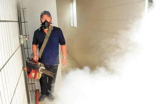 台湾登革热疫情持续延烧,防疫人员携带口罩进行消毒工作。