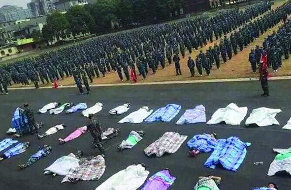 20多名女生躺在沥青跑道上,身上结结实实地裹着棉被,承受太阳的照晒和两千余名同窗的围观。