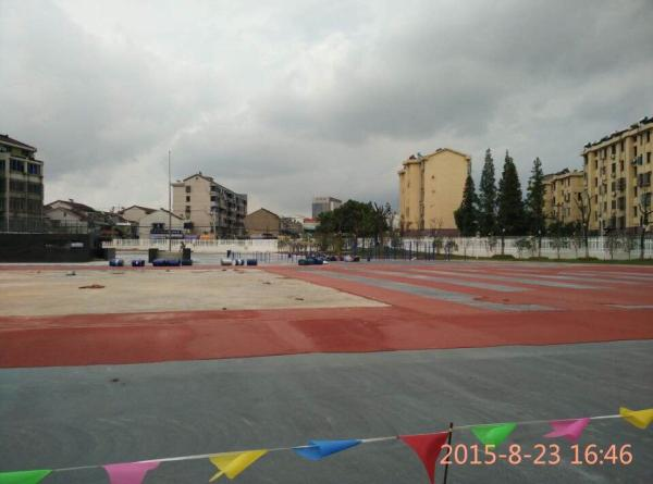 开学前夕,江阴实验小学北校区操场的塑胶跑道铺设仍在赶工中。图片由学生家长提供。