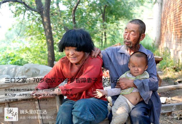 2015年9月8日,河南濮阳,王孟义全家福。拍照前,王孟义老人赶紧回到屋里,换上他最好的衣服。但疯媳妇和小庆太仿佛并不太情愿,比较别扭地被王孟义安排着。图为王孟义(右后)和他20多岁的憨傻媳妇(左)及他2岁儿子的一家合影。