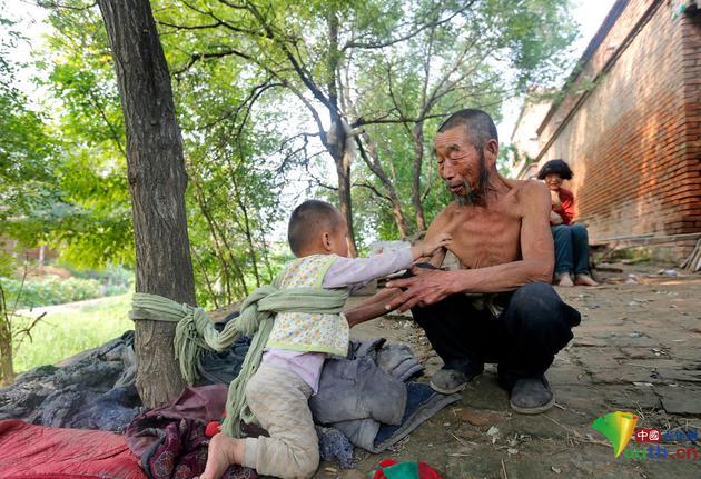 听到爸爸的声音,小庆太赶紧转身走向他的爸爸王孟义,希望爸爸能解开他身上的编织袋绳,能抱他一会儿。