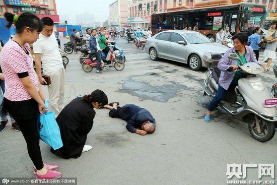 图为2015年9月19日,郑州,一位老人倒地后流血,老人倒地后无人敢扶,过路市民拍照作证。