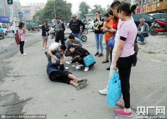 图为路人在拍照作证后,开始拨打110和120,现场一些爱心市民也走到跟前进行救助,拿着卫生纸为老人擦脸上的血迹。
