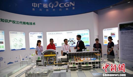 """圖為專業觀眾在中廣核展位瞭解以""""華龍一號""""為代表的中國核電技術、核燃料和核技術領域最新成果。 鐘欣 攝"""