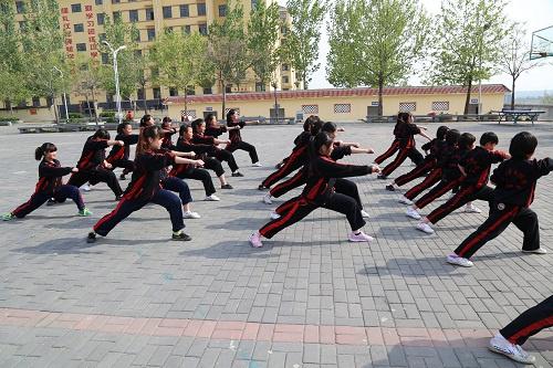 图:嵩山少林寺武术学校的女学生在训练场上认真的练习着少林功夫.