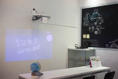 智能生活馆以意像化智能之树勾勒出科技串联生活的主题,展现出台湾智能生活产业开启的幸福一天。在模拟教室区域,Vivitek(丽讯)展示最新的无线教学协作系统,该系统是一款支持笔记本电脑、平板等多平台混合使用的高分辨率无线投影协作系统,主要由Vivitek(丽讯)超短焦互动投影机和畅享汇无线投影互动协作系统两部分组成,其中Vivitek(丽讯)D755WTIR是一款专门为教育环境量身打造的超短焦互动投影机,适用于小空间教室等场所,配备了反射式超短焦镜头,仅需0.6米即可投影80英寸大画面。它不仅继承了前作D755WTi双笔互动投影、脱离电子白板等实用功能,更加入了全新的手触功能(激光感应模组为选配),用户可在普通白板或任何白色平面上用互动笔或者手指进行操作,不仅使教学互动更加简单自由,也可有效提高教学效率,使现代教学投影应用更加人性化。