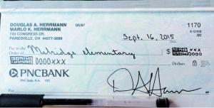 """赫曼把捐款数额依照普通核心教学标准的算法填上去,就出现了这张充满了""""Xs"""" 和""""Os""""的支票。"""