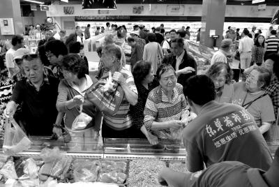 昨天,东单菜市场重新开业,生鲜肉类等商品优惠的价格吸引了大量消费者。京华时报记者王海欣摄