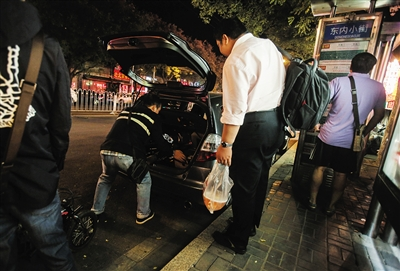 9月25日,簋街,一名代驾把自己的脚踏车放进雇主的后备厢。
