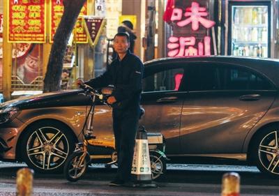 """9月25日,一名代驾在簋街的饭店门口""""等活"""",小折叠车是代驾的必备装备。A10-11版摄影/新京报记者 彭子洋"""