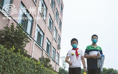 两名学生吃完晚饭,戴着口罩从宿舍楼出来前往教室自习。