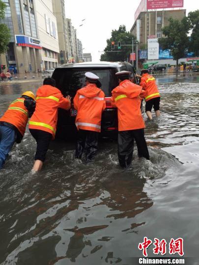 图为宁波奉化积水重大处,交警用手推积水车辆。 应伟健 摄