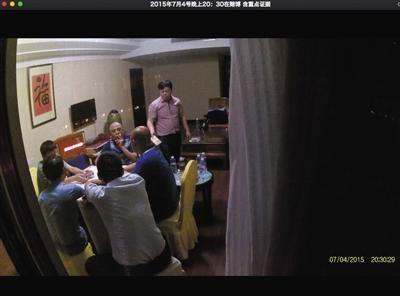 2015年7月4日,衡东县县委副书记谭建华(站立拿钱者)被偷拍到在一家酒店里赌博。视频截图