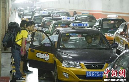 材料图:市民在北京西客站租借车候车点预备搭车。中新社发 侯宇 摄