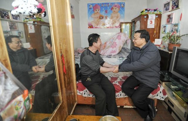 """2013年2月3日,时任国务院副总理的李克强在内蒙古包头北梁棚户区走进棚户居民高俊平家中。看到这里巷道狭窄泥泞,900多人才有一个厕所,三代同堂十几平米。李克强说:""""棚户区改造要让群众从'忧居'变'宜居',这是百姓天大的事,即使有天大的困难也要做下去。""""2013年3月17日总理记者招待会"""