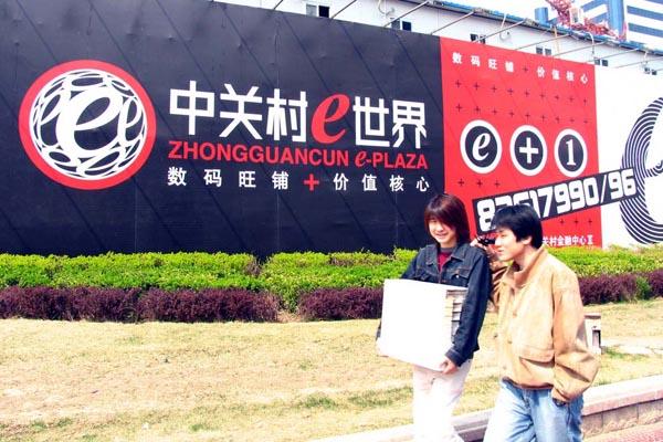 """2004年6月,几位年轻人从""""中关村e世界""""中关村金融中心宣传招租广告前走过。"""