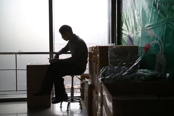 2015年1月22日,北京,中关村e世界商城。店铺工作老板无聊玩手机,待货物都装箱好后,他将搬离卖场。 CFP 图