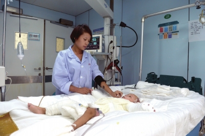 母亲在病房中关照烫坏的孩儿。京华时报记者 赵思衡 摄