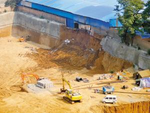 基坑坍塌招致附近的瓜果零售商场墙体也发作了崩塌 记者 付�� 摄