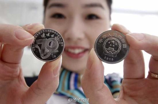 """12日上午,由中国人民银行发行的""""中国人民抗日战争暨世界反法西斯战争胜利70周年""""纪念币开始公开兑换,北京市民在多家银行网点外排队兑换纪念币。"""