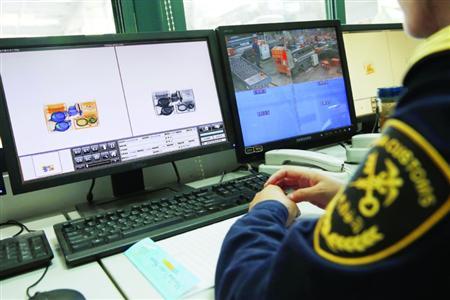 海关职员认真检察X光机传输过去的图象