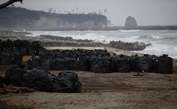 当地时间2011年3月11日,日本福岛第一核电站核灾难清理的被污染的土壤、叶子和垃圾被放入大黑塑料袋中弃置在海边。 CFP 资料