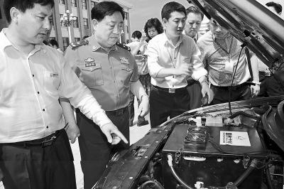 周国泰(左二)与技术人员研究超级电容器应用情况。图片来自人民日报海外版
