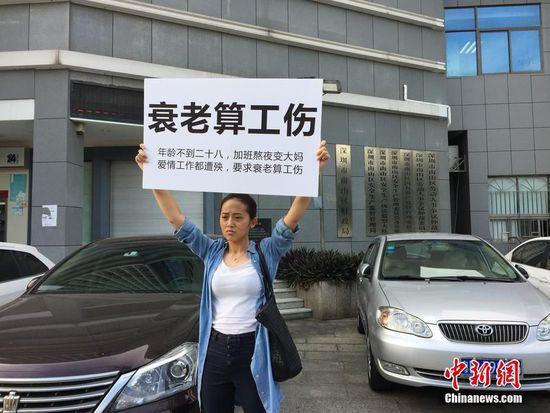 该名女白领在街头举着牌子抗议