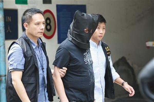 香港警方带一名疑犯到红�|民乐街案发现场重组案情。