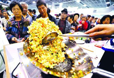 """在去年的""""江苏国际餐饮博览会""""上,厨师现场制作扬州炒饭分发给参观者品尝。/CFP"""