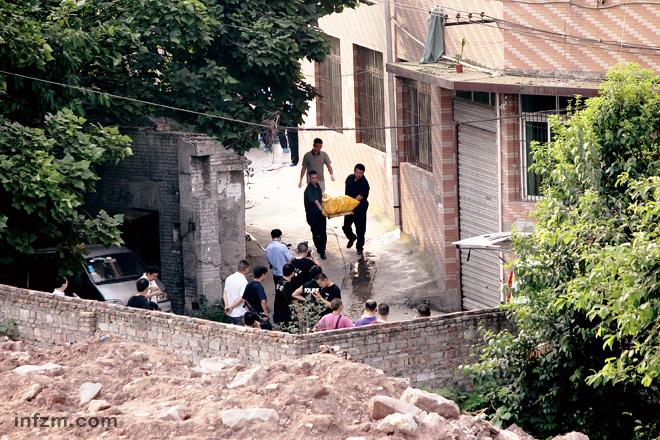 2012年8月14日,沙坪坝区童家桥,某皮鞋厂旁的一条小巷,犯罪嫌疑人周克华在这里被重庆警方击毙。警察正在将周的尸体抬离现场。 (风名/图)