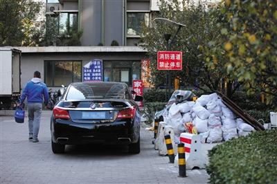 10月30日,朝阳区东恒时代小区一期,一辆汽车停放在消防通道上,旁边还堆放着建筑垃圾。 新京报记者 薛�B 摄