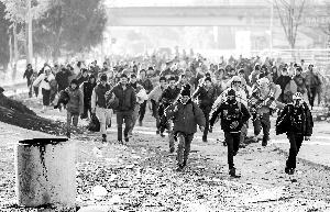 11月2日,受战事影响,中东地区难民们奔跑着穿过边境,从斯洛文尼亚申蒂利前往奥地利施皮尔费尔德。新华/法新