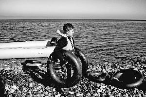 9日,在希腊的莱斯沃斯岛,一个男孩站在海滩上。他刚刚随一批难民和非法移民从土耳其乘小船到达这里。新华/法新