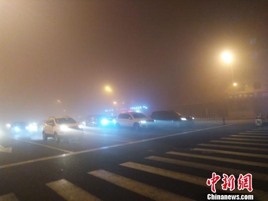 10日,一场突如其来的大雾入侵了位于中国北部的哈尔滨市。图为哈尔滨街头行驶的汽车。 王栋梁 摄