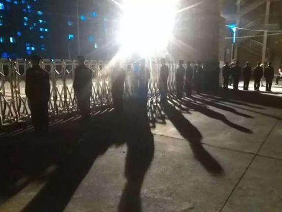 北京科技经营管理学院大门,校门口站有十多名保安。