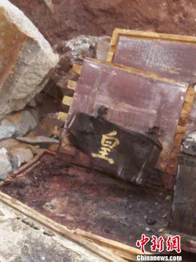 """图为裹在木棺上的红布上,用金粉写有""""皇明儒""""""""张""""、""""老""""等字样,红布被氧化后曾经酿成彩色。 严初 摄"""