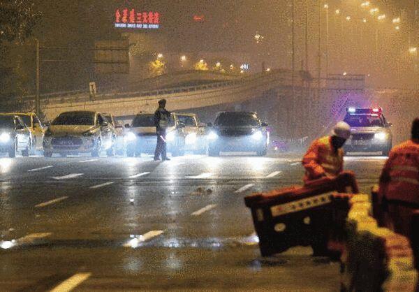 开工职员正在将阻隔栏从路途上移开,交警拦住车辆期待放行的告诉 摄/法制晚报记者郭谦