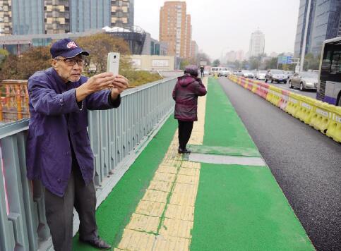 在三元桥边住了40年的老住民王大爷,看着31年的三元桥生长,昨天独特来看新桥完工,并照相留影